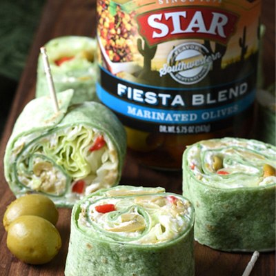 In these Olive Pinwheels, spinach flavored flour tortillas are coated with an olive and cream cheese spread, topped with scallions and lettuce, for an easy crowd-pleasing appetizer, snack, or light lunch! #STARFineFoods