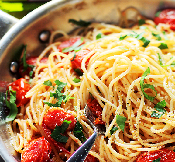 Tossed in roasted garlic oil, blistered tomatoes and a handful of parmesan cheese, this easy, 20-minute Garlic Parmesan Spaghetti recipe is absolutely delicious!  #STARFineFoods