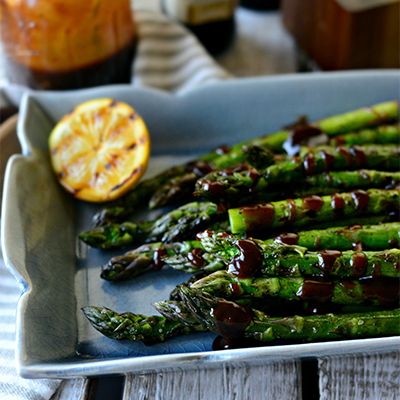 Grilled asparagus drizzled with a mildly sweet and tangy vinaigrette. This simple side recipe packs a ton of flavor! #STARFineFoods