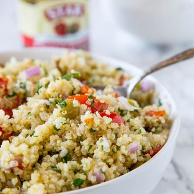 A light and fresh quinoa salad made with tomatoes, our Reduced Sodium Pimiento Stuffed Manzanilla Olives and tossed with a lemon vinaigrette. This dish is great served warm or cold, all year round! #STARFineFoods