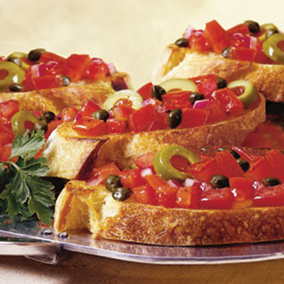 Easy to make and delicious. This Olive Bruschetta recipe combines fresh tomatoes, capers, olive oil, vinegar, garlic, and olives to make a flavorful topping on fresh bread. #STARFineFoods