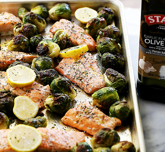 Incredibly delicious, garlicky, super flavorful one-pan dinner with oven-roasted salmon and Brussels sprouts. #STARFineFoods