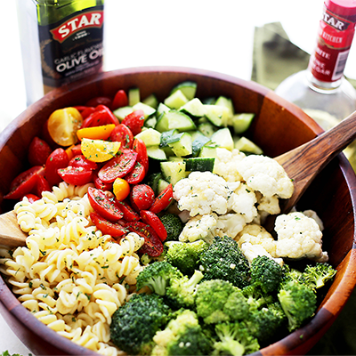 Quick and easy recipe to make Potluck Pasta Salad packed with broccoli, tomatoes, cucumbers and cauliflower, all tossed in a zesty and delicious homemade Dijon Vinaigrette! #STARFineFoods