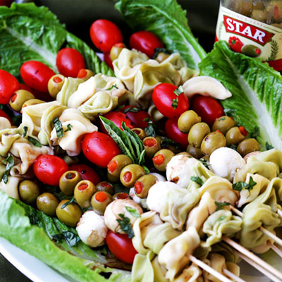 Fun and festive appetizer plate with cheesy tortellini, flavorful manzanilla olives, grape tomatoes and fresh mozzarella cheese threaded on skewers.  #STARFineFoods