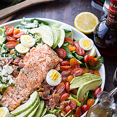 This Salmon Cobb Salad recipe is filled with tender spinach and romaine lettuce, topped with a delicious oven-baked salmon, tomatoes, eggs, bacon, avocados and feta cheese. #STARFineFoods